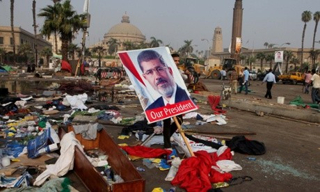 An Egyptian carries a poster of Egypt's ousted President Mohammed Morsi among debris from a protest camp in Nahda Square, Giza, Cairo, Egypt, Thursday, Aug. 15, 2013. (AP Photo/Amr Nabil)