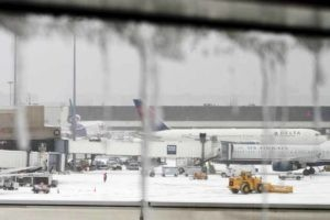 Icicles on a window are seen in front of airplanes during a winter nor'easter snow storm in Boston