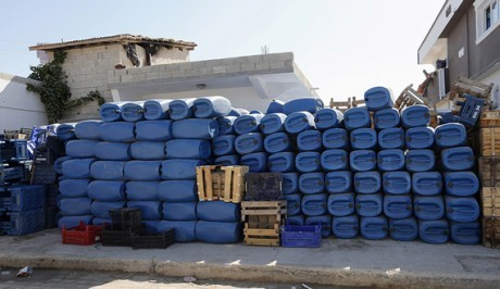 Blue jerry cans usually used by smugglers ferrying fuel smuggled into Turkey from over the border in Syria are stacked in front of a shop for sale in Turkish border town of Hacipasa, Hatay province, September 8, 2013. - source, Al-Monitor